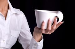 Cup of tea. A female hand proposing a cup Stock Photo