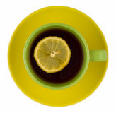 Cup of tea. Green cup of tea on the yellow saucer stock photo