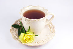 A cup of tea. Yellow rose on nice cup of tea on white background royalty free stock photography