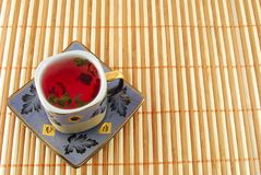 Cup of tea. Cup of red tea on the striped rug stock photos