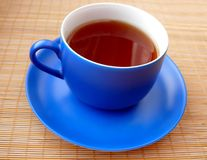 Cup of tea. Tea in blue cup on bamboo mat stock image
