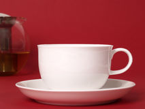 A cup of tea. With a tea pot in the background on a red background Royalty Free Stock Photos