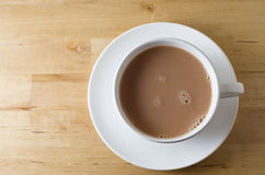 Cup of Tea from Above. Overhead shot of a cup of tea, with saucer on old, scratched light wooden table with copy space to left. Landscape (horizontal) stock images