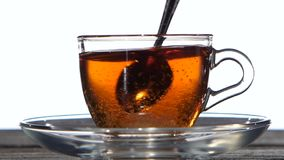 In cup of tea add sugar spoon. Closeup. Slow motion. In cup of tea which stands on a wooden table add sugar spoon, transparent cup on the saucer, of hot drink stock video