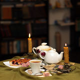 Cup of tea against a background. Of burning candles, cake, flowers and old photographs Royalty Free Stock Photo