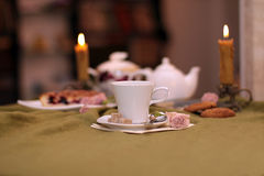 Cup of tea against a background of candles and pie. Cup of tea against a background of burning candles, pie, flowers and old photographs Stock Photos
