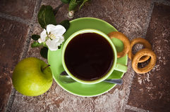 Cup of tea with an apple Stock Image