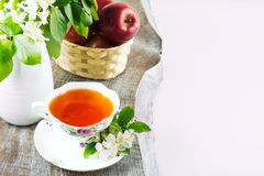 Cup of tea and apple blossom in vase. Tea cup and apple blossom in vase on the rustic table copy space Stock Photo