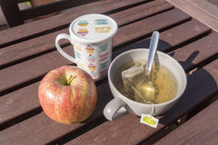 Cup of tea with apple, breakfast in the garden Stock Photography