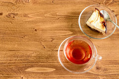 Cup of tea and apple cake on wooden desktop with copy space. A cup of black tea in a transparent glass cup, and apple cake with spoon on rustic wooden table top Stock Images
