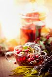 Cup of tea with autumn leaves and berries at sunny nature background on wooden table., front view. Hot autumn beverages Stock Image