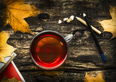Cup of tea with autumn leaves, books and pencils on wooden background, top view Royalty Free Stock Photos