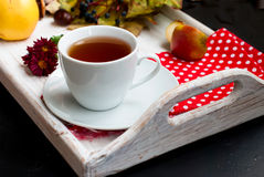 Cup of tea with autumn leaves of wild grapes Stock Photos