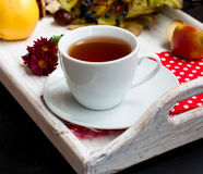 Cup of tea with autumn leaves of wild grapes Stock Image