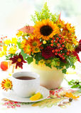 Cup of tea and autumnal flowers Royalty Free Stock Images