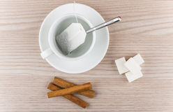 Cup with tea bag, cinnamon sticks and pieces of sugar Stock Images