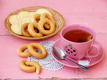 Cup of tea, bagels and cookies. On a pink background royalty free stock photography