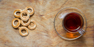 Cup of tea, bagels dry on the old rustic table wood background. Royalty Free Stock Photography