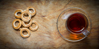 Cup of tea, bagels dry on the old rustic table wood background. Royalty Free Stock Images