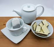 Cup with tea bags, teapot and chocolate wafers on wooden table, white background stock photography