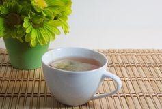 Cup of tea on bamboo with green flowers Royalty Free Stock Photography