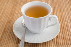 A cup of tea on bamboo mat Royalty Free Stock Image