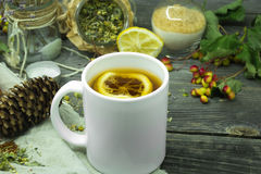 The Cup of tea on a beautiful wooden background with lemon and herbs, winter ,autumn Stock Photography