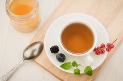 Cup of tea with berries and mint in a saucer and honey/cup of tea with berries and mint in a saucer and jar of  honey on a wooden. Tray. Top view open currant royalty free stock photo