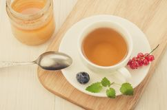 Cup of tea with berries and mint in a saucer and honey/cup of tea with berries and mint in a saucer and honey on a wooden tray. Top view jar open currant royalty free stock photography