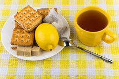 Cup of tea, biscuits and lemon in plate Stock Photo