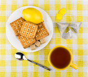 Cup of tea, biscuits and lemon in plate on table Stock Image
