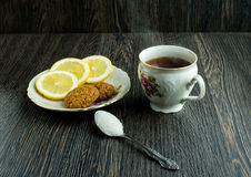 Cup of tea with biscuits and lemon on top, hot tea with lemon and sugar Royalty Free Stock Image