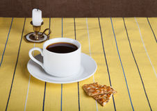 Cup of tea with biscuits and retro style candle on the striped y Royalty Free Stock Image