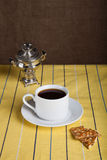 Cup of tea with biscuits and samovar on the striped yellow table Royalty Free Stock Photography