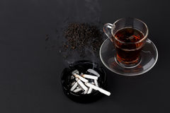 Cup of tea and black ashtray with cigarettes Stock Images