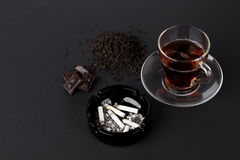 Cup of tea black ashtray cigarettes chocolate Stock Images
