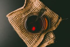 Cup of tea on a black background. A glass cup of tea on the black background and a sackloth stock images
