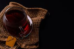 Cup of tea on a black background. A glass cup of tea on the black background and a sackloth stock photography