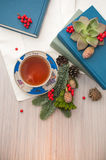 A cup of tea. A cup of black tea, books and coniferous winter composition with pine cones and rowan. Light background Royalty Free Stock Image