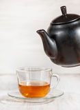 Cup of tea and black teapot Royalty Free Stock Photos