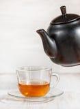 Cup of tea and black teapot Royalty Free Stock Photos