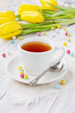 Cup of tea with bonbon and a spring flowers Stock Images