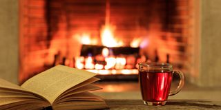 Cup of tea and a book on a burning fireplace background Stock Image