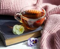 Cup of tea, book and flowers on light wooden background. Reading concept.