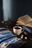Cup of tea, book and knit cap on wooden table stock image