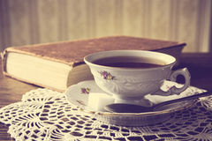 Cup of tea with book on napkin vintage effect Stock Photography