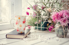 Cup of tea with a book and pink flowers Stock Photos