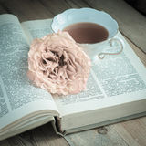 Cup of tea, a book and a rose. On wooden table Royalty Free Stock Images