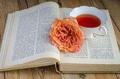 Cup of tea, a book and a rose. On wooden table Royalty Free Stock Image