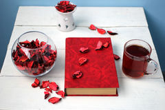 Cup of tea with a book and a vase of rose petals. On the dazzling white table Stock Photo